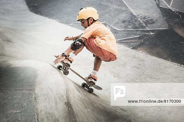 Mixed race boy riding skateboard in skate park Mixed race boy riding skateboard in skate park