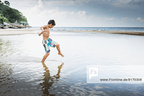 Mixed race boy playing in water on beach