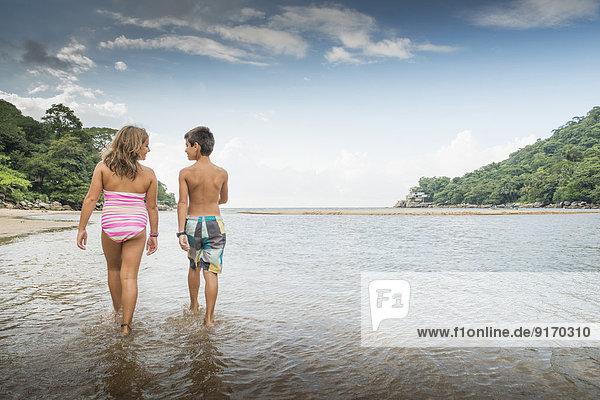 Children walking together in water Children walking together in water