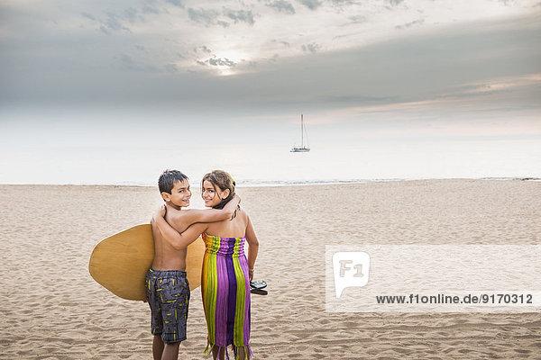 Mixed race children carrying surfboard to ocean