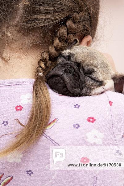 Mixed race girl hugging pug