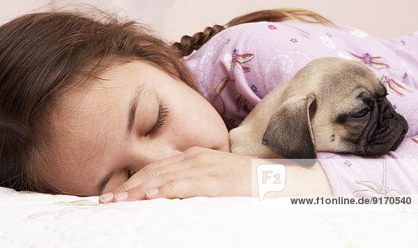 Mixed race girl sleeping with pug