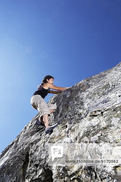 Hispanic climber scaling steep rock face