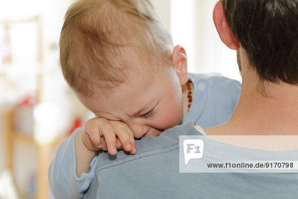 Father holding crying baby boy