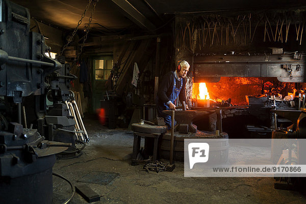 Germany  Bavaria  Josefsthal  senior blacksmith at work in historic blacksmith's shop