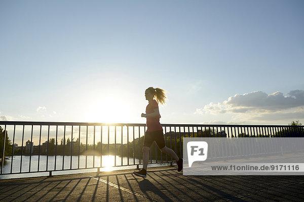 Junge Frau beim Joggen über die Brücke im Gegenlicht
