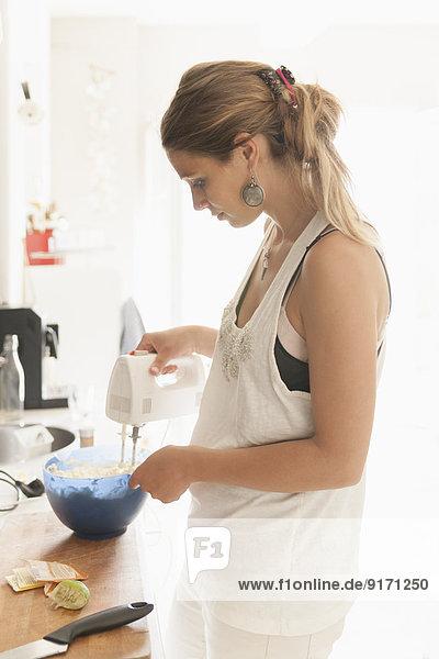 Young woman mixing dough at kitchen
