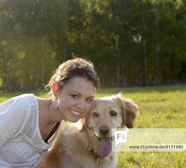 Bildnis einer jungen Frau mit Golden Retriever auf der Wiese