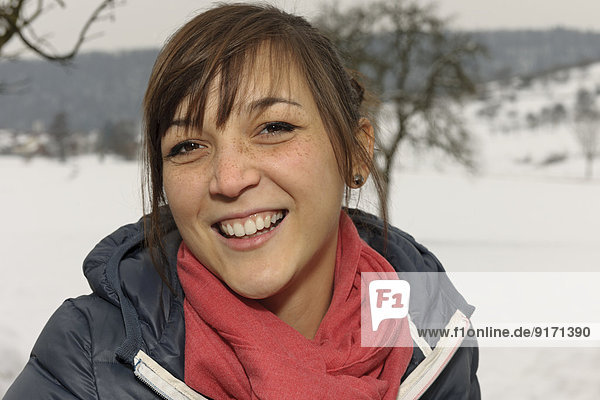 Portrait of laughing young woman with freckles in winter