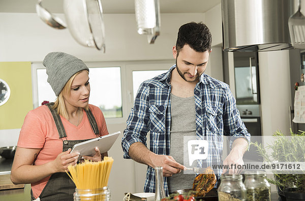 Couple cooking in kitchen at home