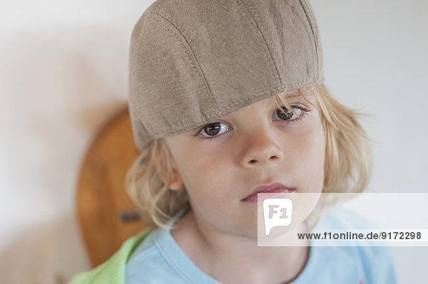 Seriöser blonder Junge mit Mütze