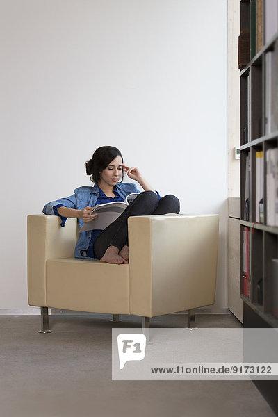 Porträt einer Geschäftsfrau  die auf einem Sessel sitzt und das Magazin liest.