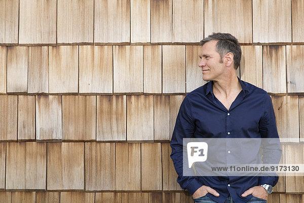 Porträt des kreativen Geschäftsmannes vor Holzschindelverkleidung