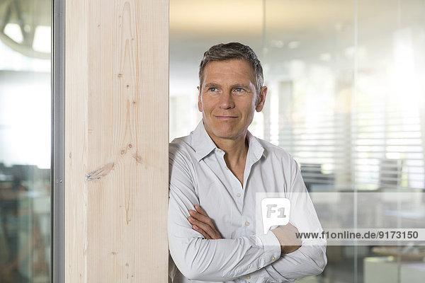 Porträt eines lächelnden kreativen Geschäftsmannes mit gekreuzten Armen vor der Glasscheibe