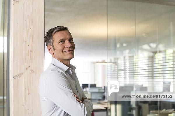 Porträt eines lächelnden  kreativen Geschäftsmannes vor dem Büro