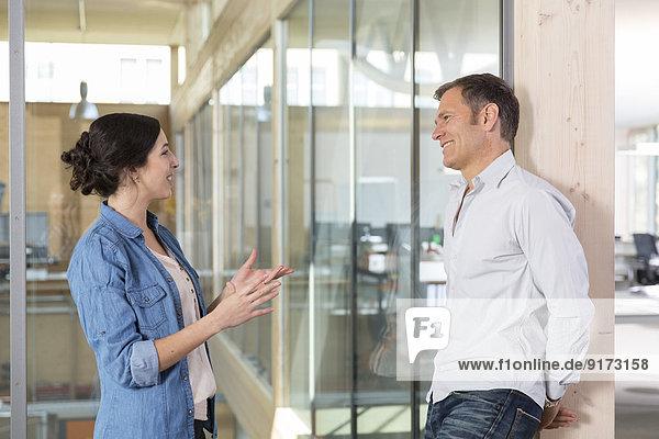 Porträt von zwei Geschäftsleuten  die vor der Glasscheibe kommunizieren