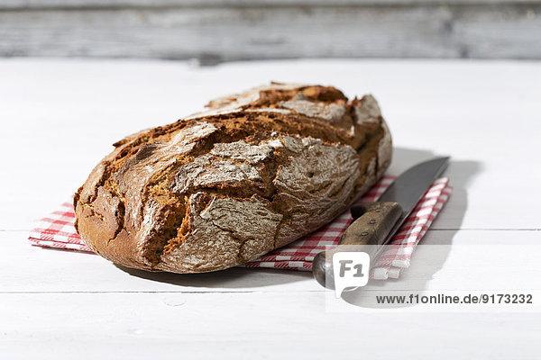 Knuspriges Brot und Messer auf Stoff und weißem Holz