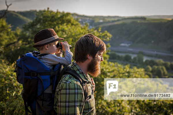 Germany  Rhineland-Palatinate  Moselsteig  father and his little son looking at view with binocular