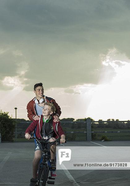 Zwei Jungs mit BMX-Bike und Kopfhörer