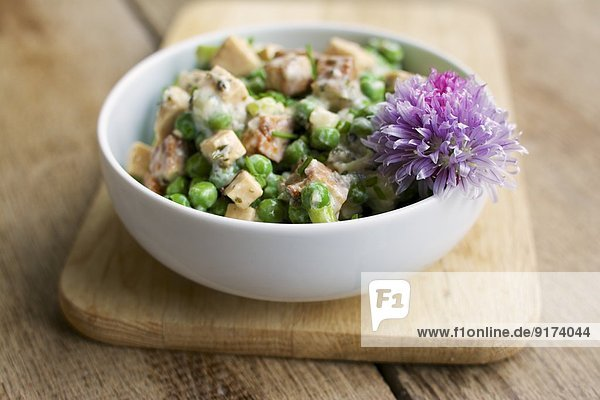 Creamy pea salad with spicy tofu pieces  soy yogurt  chives and mint