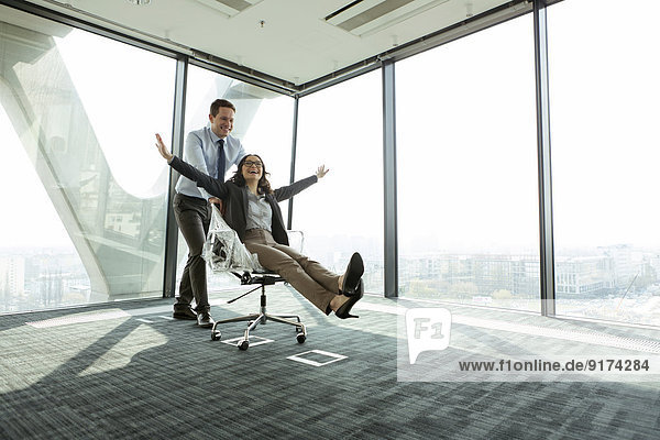 Geschäftsmann schiebt Geschäftsfrau in Bürostuhl