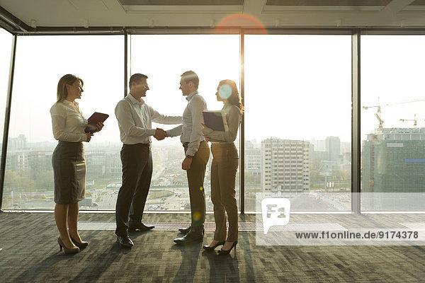 Zwei Geschäftsleute im sonnigen Büro mit Händeschütteln