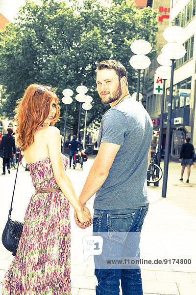 Deutschland  Bayern  München  junges Paar steht Hand in Hand in der Fußgängerzone