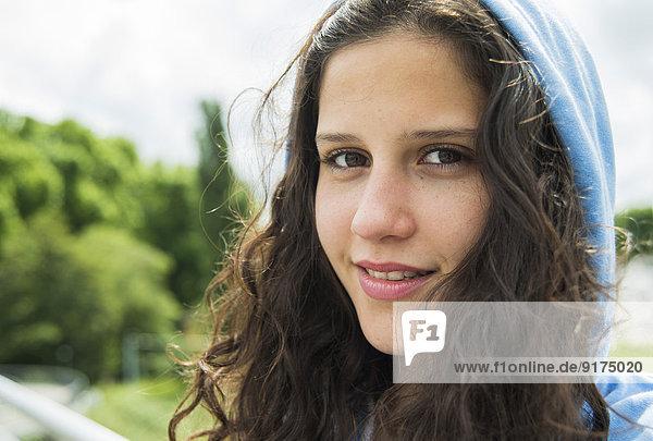 Porträt einer lächelnden jungen Frau mit Kapuze