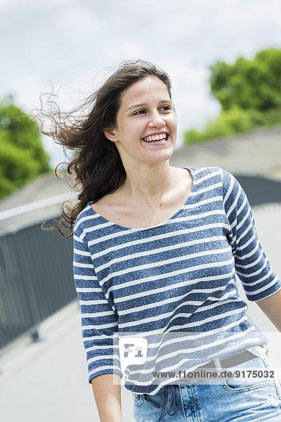 Porträt einer lächelnden jungen Frau mit wehendem Haar