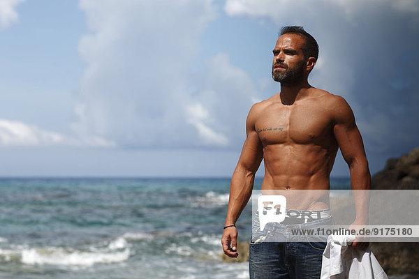 Griechenland  Ionische Inseln  Korfu  Mann ohne Hemd  der das Sonnenlicht vor dem Meer genießt