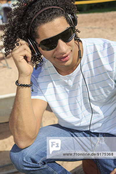 Portrait of a young man listening music on the beach