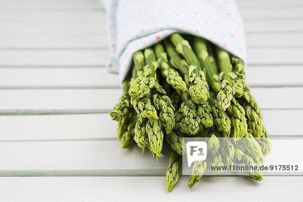 Grüner Spargel  Asparagus officinalis  in Tuch gewickelt  auf weißem Holz liegend
