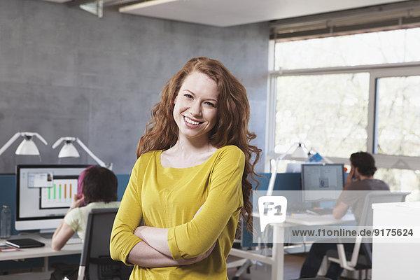 Porträt einer lächelnden jungen Frau im Großraumbüro