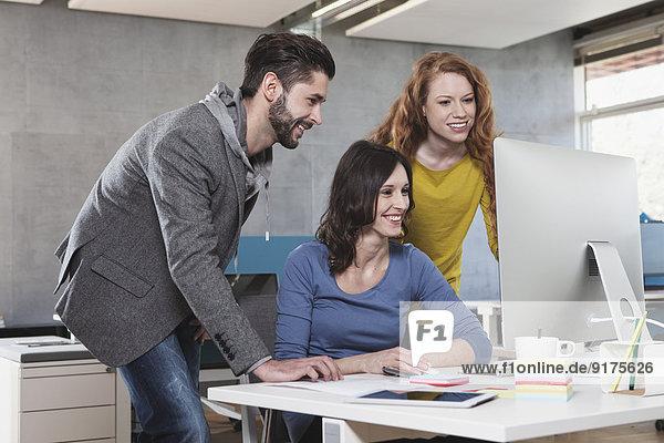 Drei Kollegen beim Blick auf den Computer im Büro