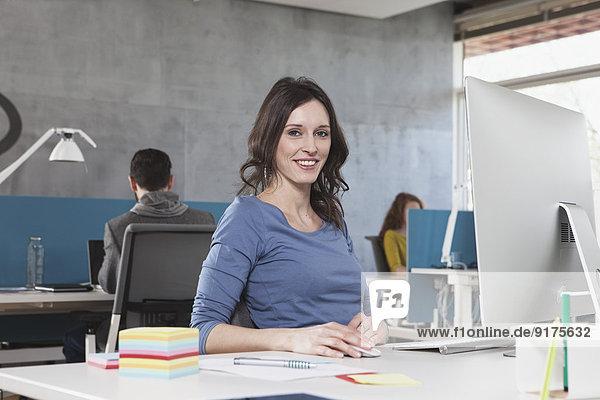 Porträt einer lächelnden Frau an seinem Arbeitsplatz im Büro
