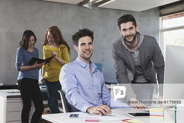 Vier Kollegen in einem Großraumbüro