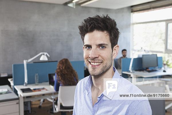 Porträt eines lächelnden Mannes im Großraumbüro