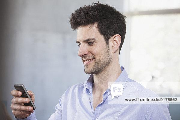 Porträt eines lächelnden Mannes auf seinem Smartphone