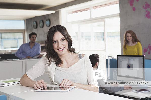 Porträt einer lächelnden Frau mit digitalem Tablett im Großraumbüro