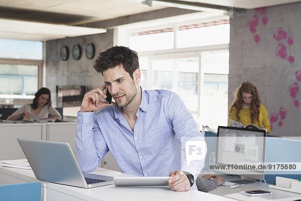 Porträt eines Mannes mit Laptop-Telefonie mit seinem Smartphone im Großraumbüro