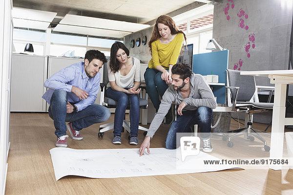 Vier Kollegen diskutieren im Büro über eine Konzeption