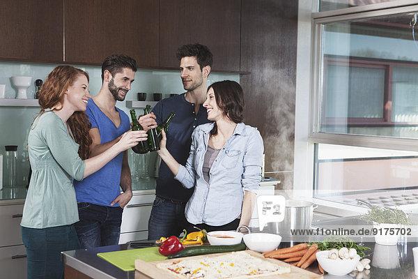 Porträt von vier Freunden  die mit Bierflaschen in der Küche anstoßen.