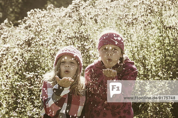 Two girls blowing seeds from shrub
