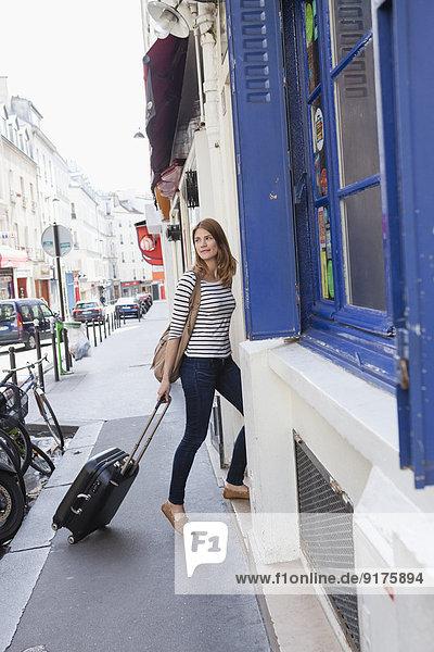 Frankreich  Paris  Porträt einer jungen Frau mit rollenden Koffern im Hotel