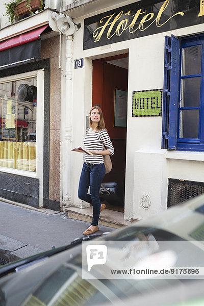 Frankreich  Paris  Porträt einer jungen Frau mit rollendem Koffer beim Verlassen des Hotels