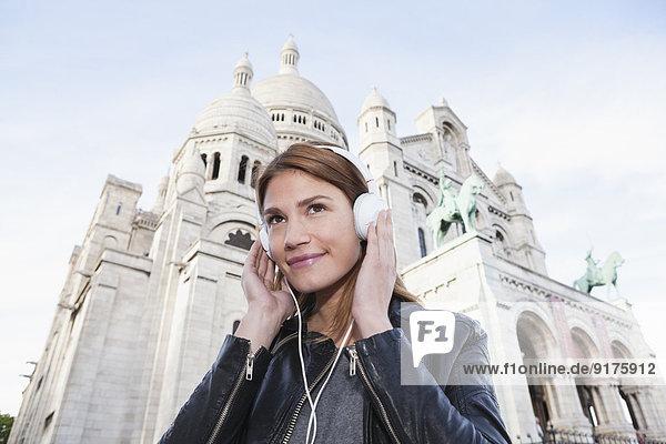 Frankreich  Paris  Porträt einer lächelnden jungen Frau beim Musikhören mit Kopfhörern vor Sacre Coeur Frankreich, Paris, Porträt einer lächelnden jungen Frau beim Musikhören mit Kopfhörern vor Sacre Coeur