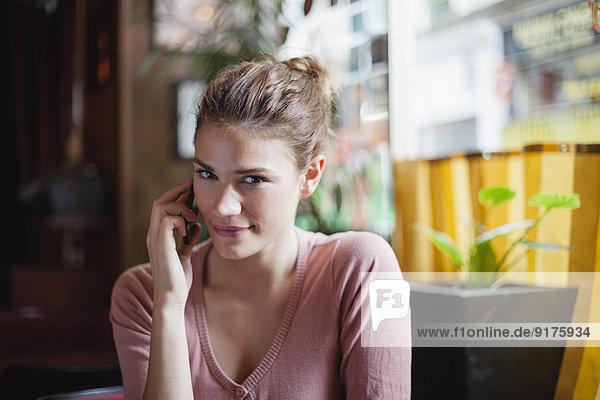 Frankreich  Paris  Porträt einer jungen Frau  die mit ihrem Smartphone in einem Café telefoniert.