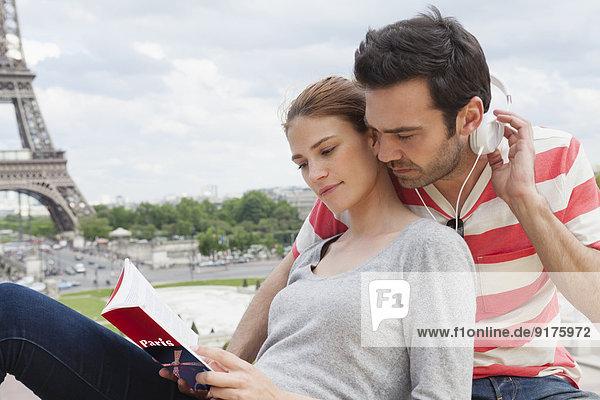 Frankreich  Paris  Portrait des Paares mit Reiseführer und Kopfhörer vor dem Eiffelturm