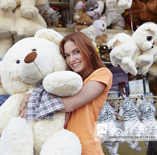Fröhliche junge Frau auf einem Jahrmarkt  die einen großen Teddybären umarmt.