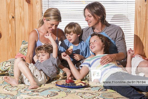 USA  Texas  Familie mit Obstschale auf dem Bett